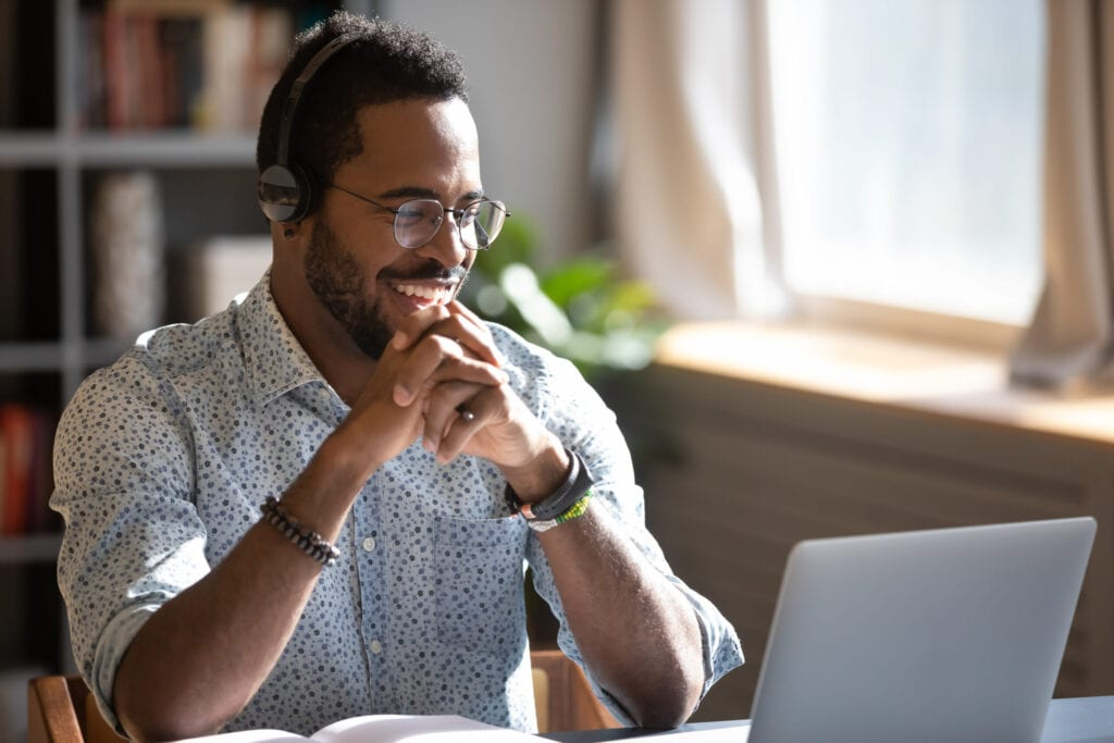 Man smiling at laptop with headphones on