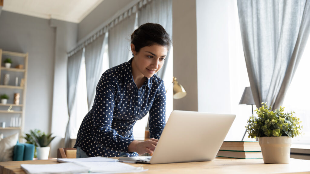 Woman standing at desk using her laptop