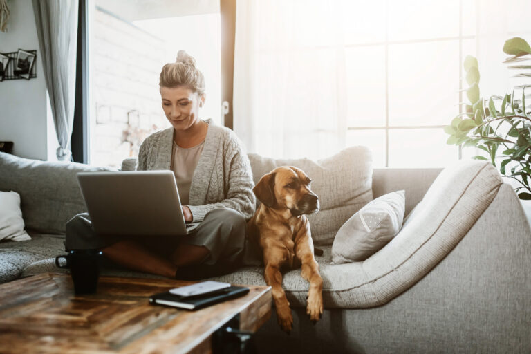 Woman on laptop with dog next to her, both on the sofa