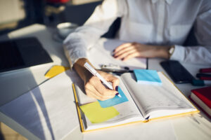 Woman writing on post-it notes at desk